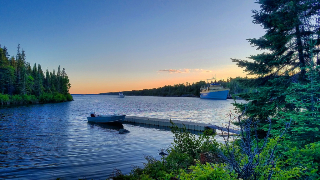 A large blue boat is in the far right of the frame with a simple pinkish sunset behind it. In the foreground is a dock with a small boat with trees and shrubs on both sides of the frame.